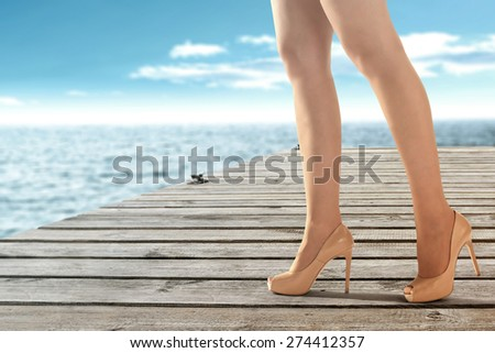 woman legs on wooden pier and sea