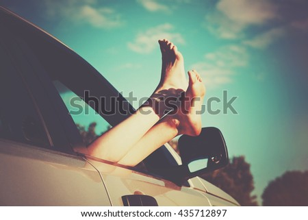 Woman legs out car window. Freedom or traveling concept