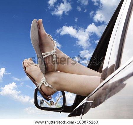 Woman legs out the windows in car above the clouds.