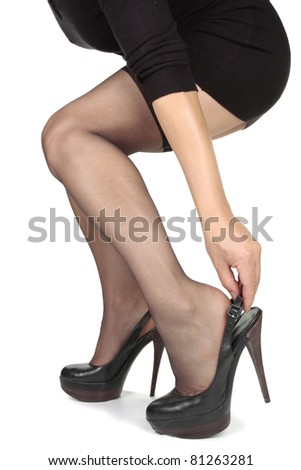 Woman legs  putting on heels  shoes over white