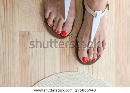 Woman legs putting on shoes with accessories