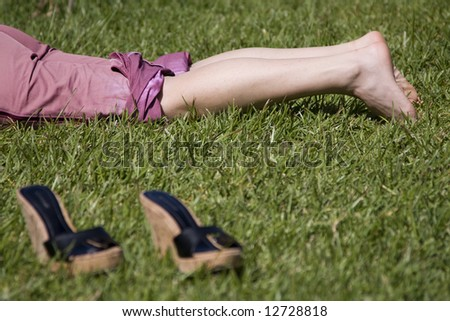 woman legs resting in the grass (selective and soft focus) - stock photo