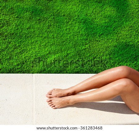 Woman legs sunbathing by green lawn