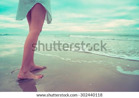 Woman legs walking on the beach.Vintage filter. - stock photo