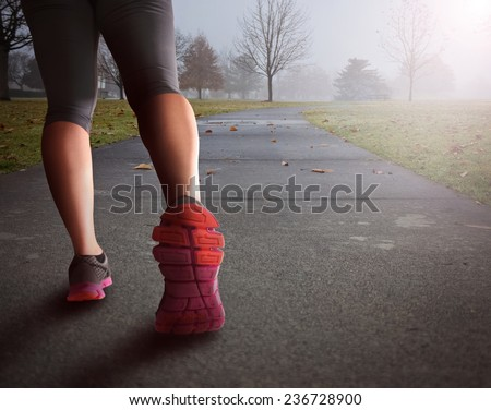 woman legs walking path in park in fog covered morning background - stock photo
