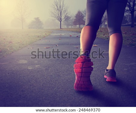 woman legs walking path in park in fog covered morning background with retro instagram filter (shallow depth of field) - stock photo