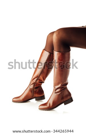 woman legs wearing brown leather high boots, isolated on white - stock photo