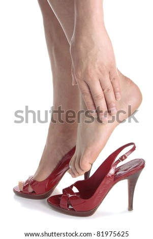 Woman legs wearing high heels massaging aching feet over white background - stock photo