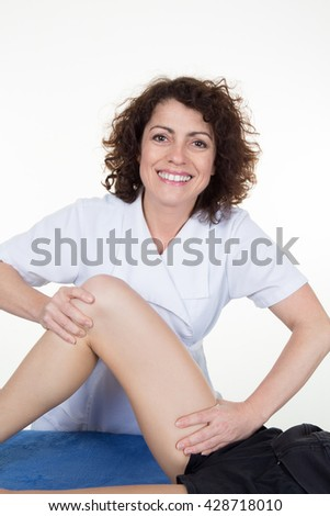 Woman legs while being massaged by a woman therapist - stock photo