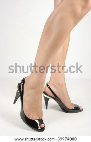 Woman legs with black high heel shoes over white