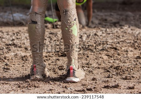 woman legs with dirty socks with mud on extreme run - stock photo