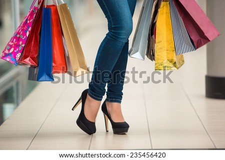Woman legs with shopping bags against the backdrop of a shopping center - stock photo
