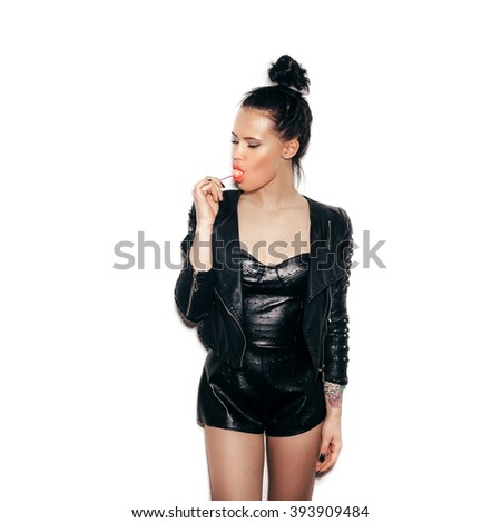 Woman licking a red shiny lollipop. Close up against white background, not isolated - stock photo