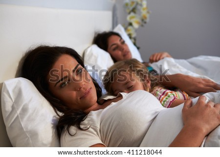 Woman lies awake while her daughter and female partner sleep - stock photo