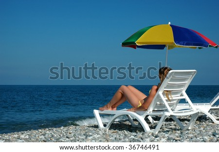 Woman lies in chaise lounge on beach