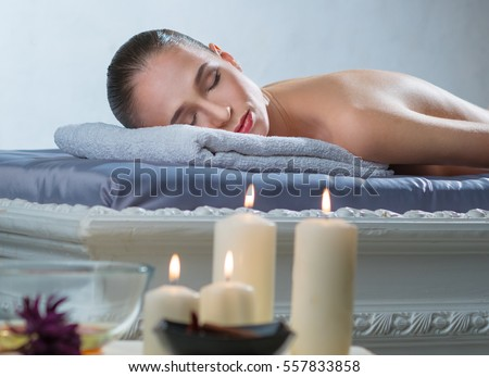 Woman lies on a massage table in a spa - salon