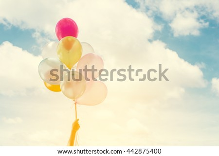 Woman lifestyle concept: woman hands holding a bunch of colored balloons with blue sky summer time enjoy life. - stock photo