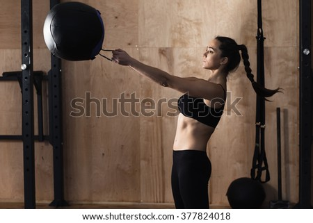 Woman lift weight ball at the gym - stock photo