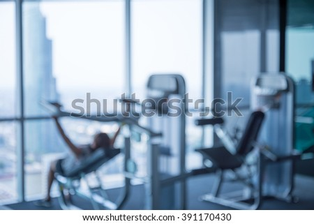 Woman lift weights in modern luxury fitness center city view abstract blur background
