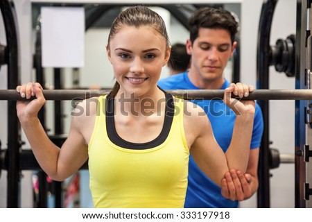 Woman lifting barbell with trainer spotting her at the gym - stock photo