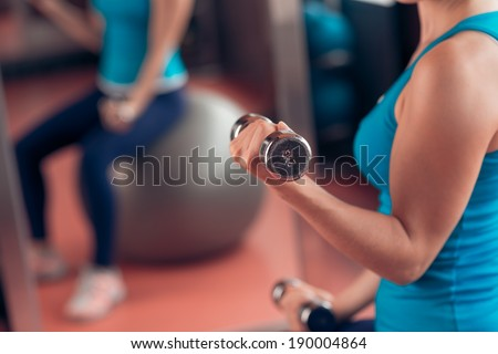 Woman lifting dumbbells in the gym - stock photo