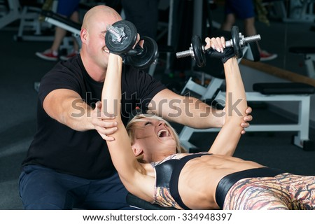 Woman lifting dumbbells with her personal trainer in the gym. Weightlifting in sports club.
