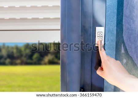 Woman lifting electric shutters in house - stock photo