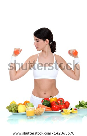 Woman lifting  weights surrounded by vegetables - stock photo