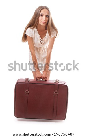 woman lifts a heavy suitcase, isolated on white background