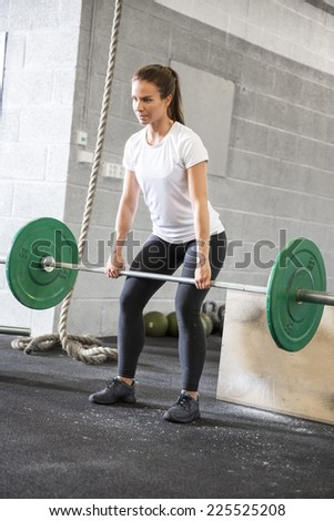 Woman lifts deadlift at the fitness gym - stock photo