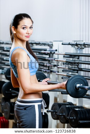 Woman lifts dumbbells in sport centre to develop muscles - stock photo
