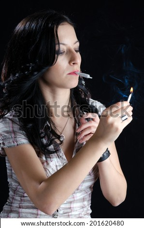 Woman Lighting Up a Cannabis Joint - stock photo