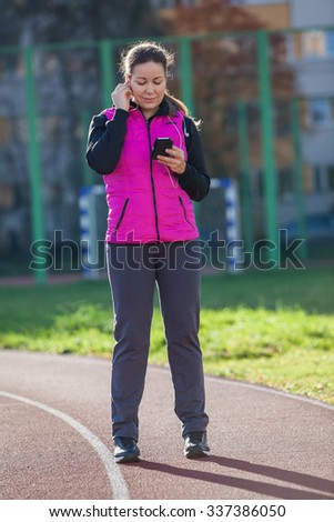 Woman listen the music with mobile phone while standing at the running track of the stadium - stock photo