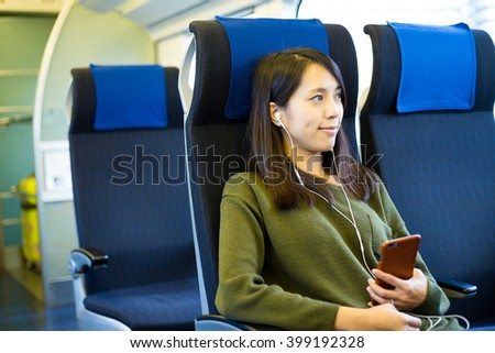 Woman listen to music on mobile phone inside train compartment - stock photo