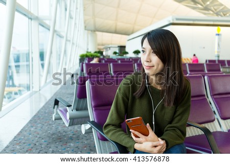 Woman listen to music with cellphone at terminal gate