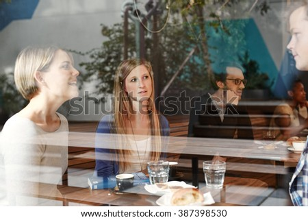 Woman listening as friends talk at a busy modern cafe - stock photo