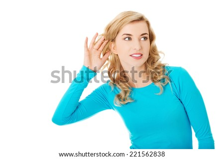 Woman listening gossip with her hand next to her ear - stock photo