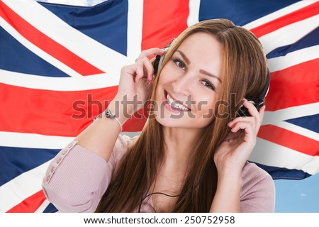 Woman Listening Language Learning Course Audiobook In Front Of British Flag - stock photo
