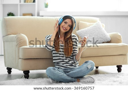 Woman listening music in headphones in room