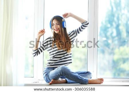 Woman listening music in headphones on windowsill background - stock photo