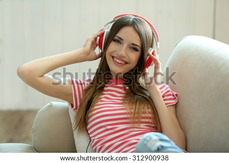 Woman listening music in headphones while lying on sofa in room - stock photo