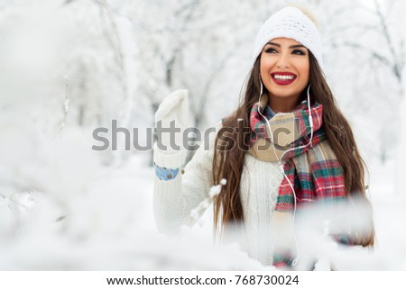 Woman listening music with her mobile phone in first snow