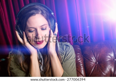 Woman listening to headphones in a club - stock photo