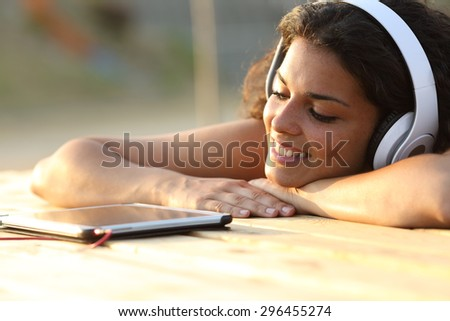 Woman listening to music from a tablet watching the screen in a park at sunset - stock photo