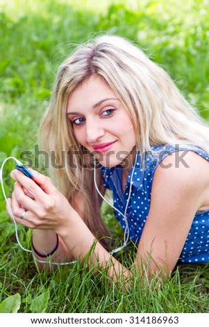 Woman listening to music lying on the grass in the park.