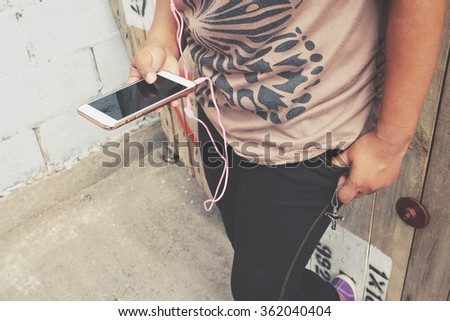 Woman listening to music on earphone with smart phone and cross
