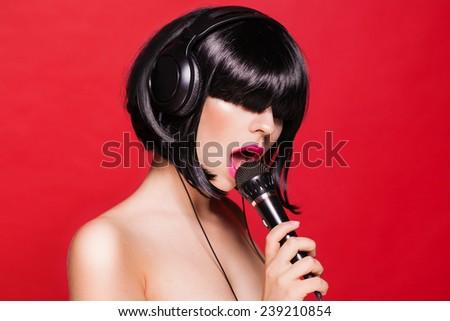 Woman listening to music on headphones enjoying a dance. Closeup portrait of beautiful girl with pink lips - stock photo