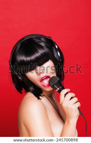Woman listening to music on headphones enjoying a singing. Closeup portrait of beautiful girl with pink lips. Karaoke. on red background - stock photo