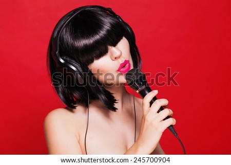 Woman listening to music on headphones enjoying a singing. Closeup portrait of beautiful girl with pink lips - stock photo