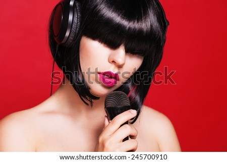 Woman listening to music on headphones enjoying a singing. Closeup portrait of beautiful girl with pink lips. Karaoke - stock photo